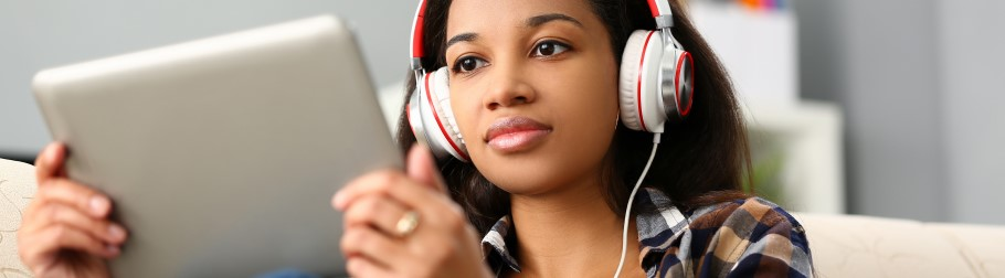Image of a student reading a blog and listening to music
